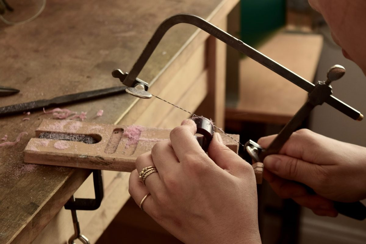 Shuang cutting metal at her workbench