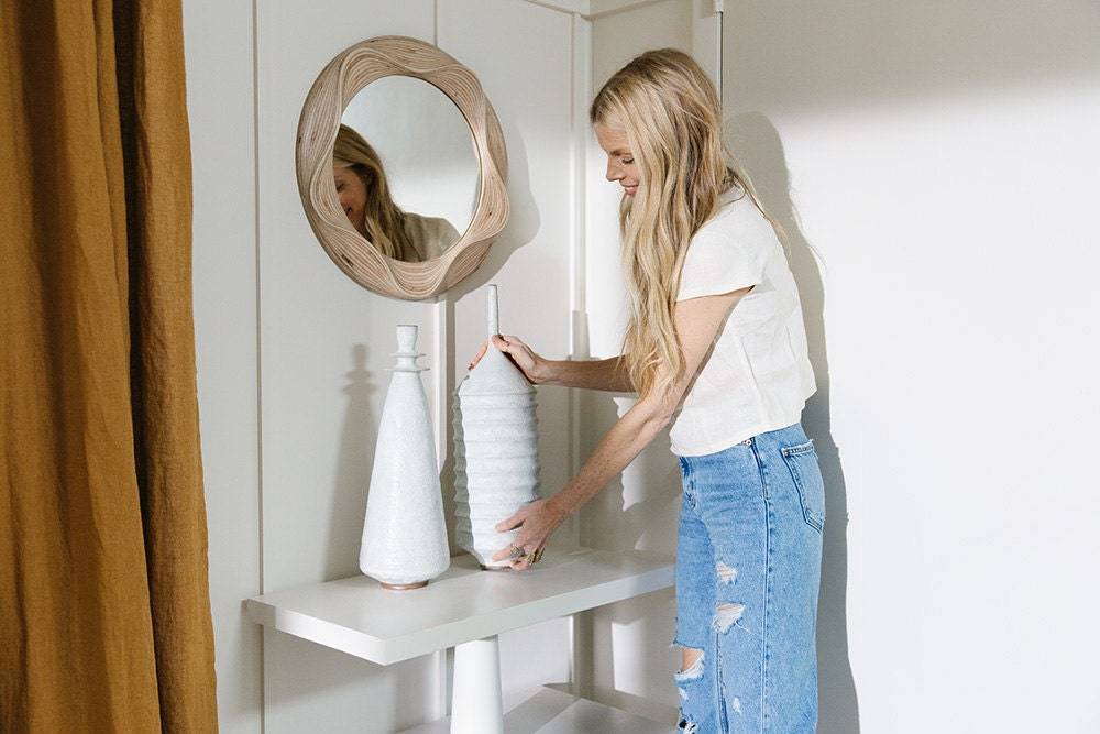 Sarah arranges ceramic sculptures on a white shelf. Above the shelf is a round wooden mirror with a raised, wavy design.
