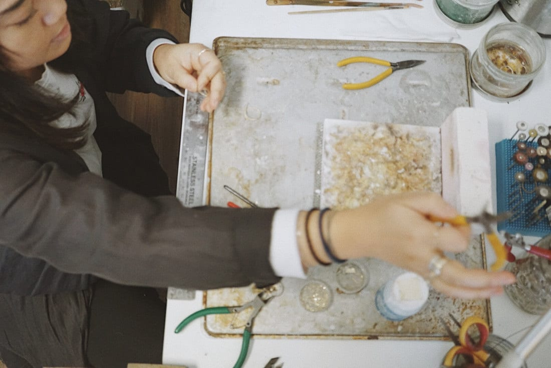 Katherine selects the proper pair of pliers to begin work on one of her gold jewelry pieces.