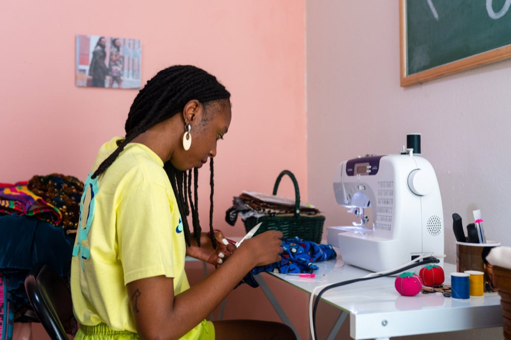 Rachelle mending a vintage garment at her sewing machine.