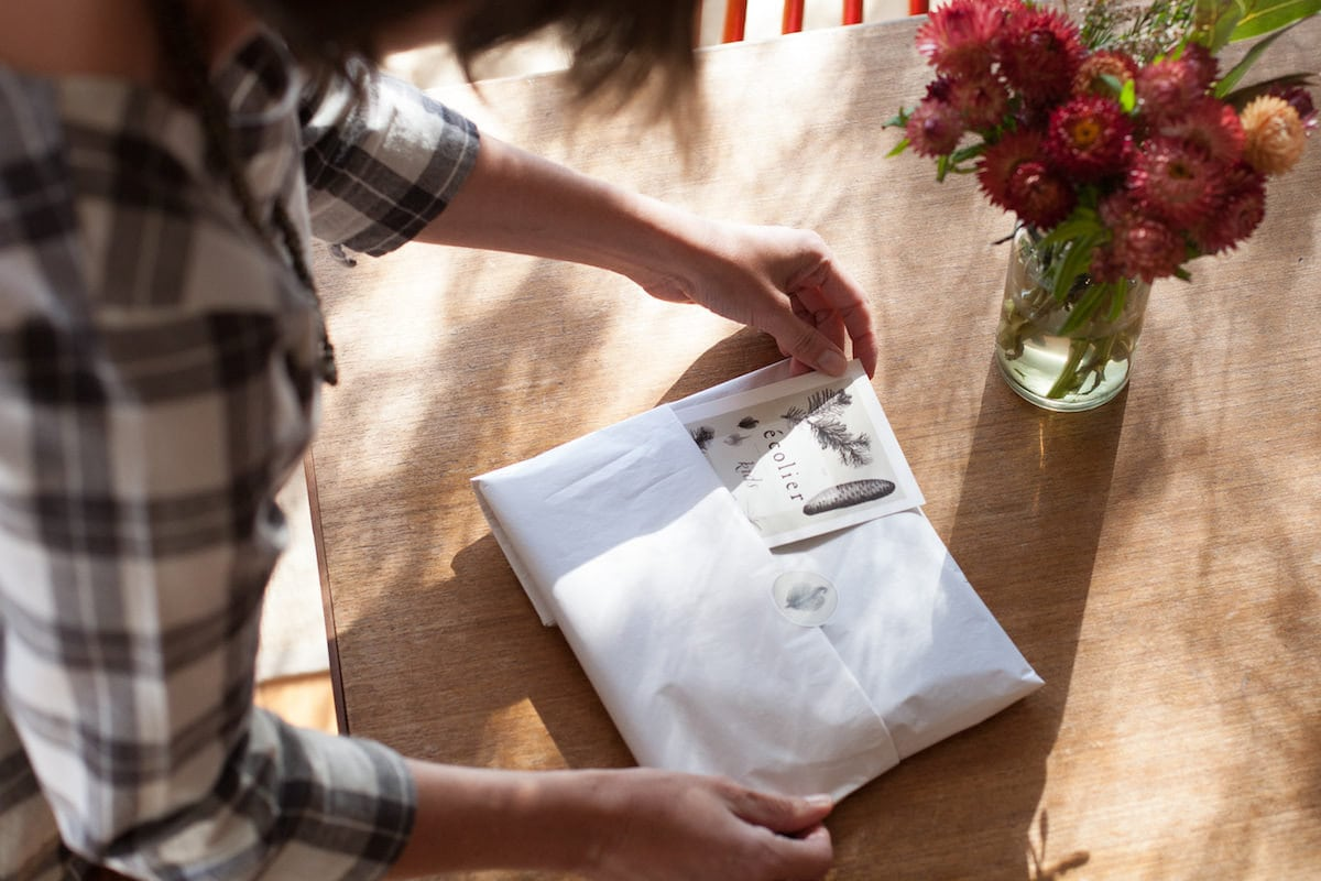 Madeline packaging an order in her sunny studio