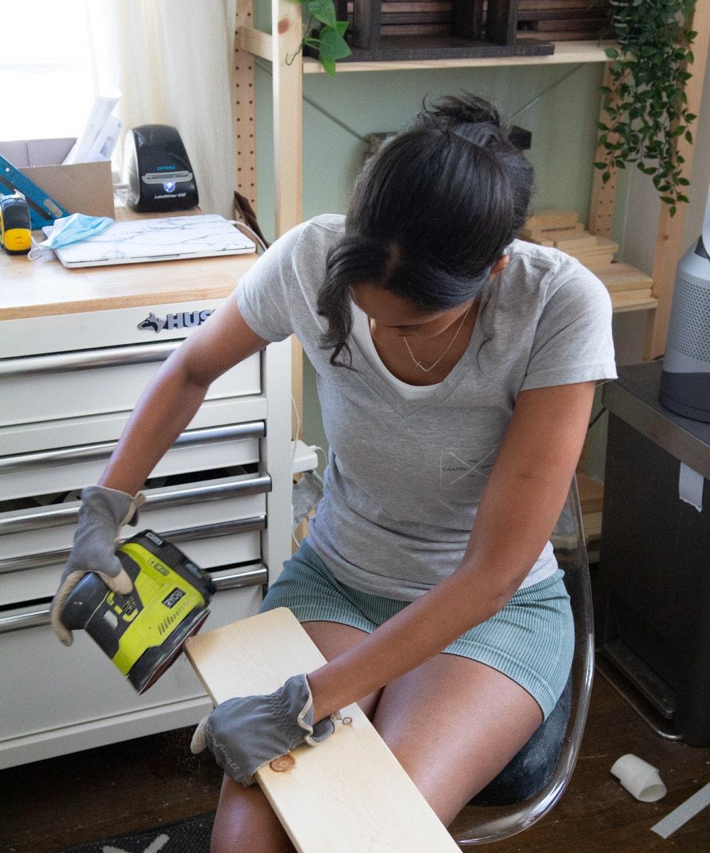 Ilana sands a cut of wood.