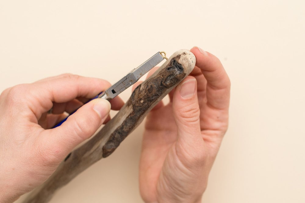 Screwing a small eye hook into the end of the piece of driftwood