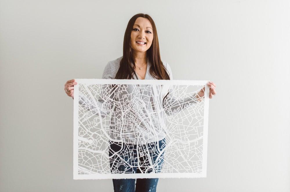 Karen holding a large paper-cut map