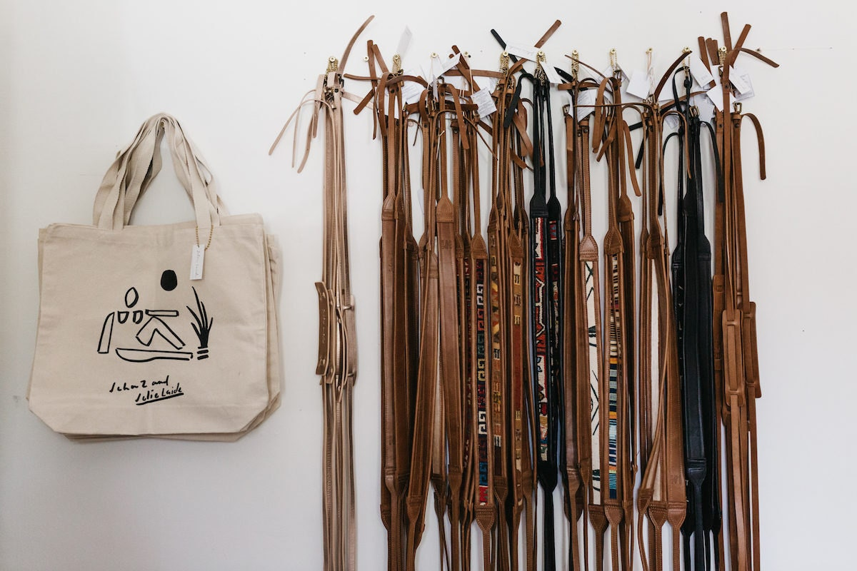 Leather camera straps and canvas tote bags hanging on a wall
