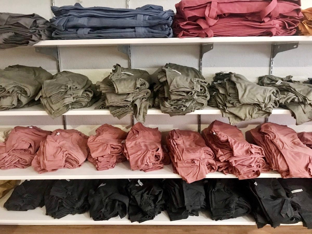 Blank tees and totes in assorted colors line the shelves of Lindsey's studio