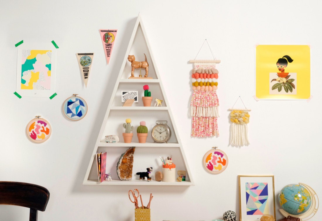 A shelf styled with colorful school supplies and framed by lots of vibrant wall art.
