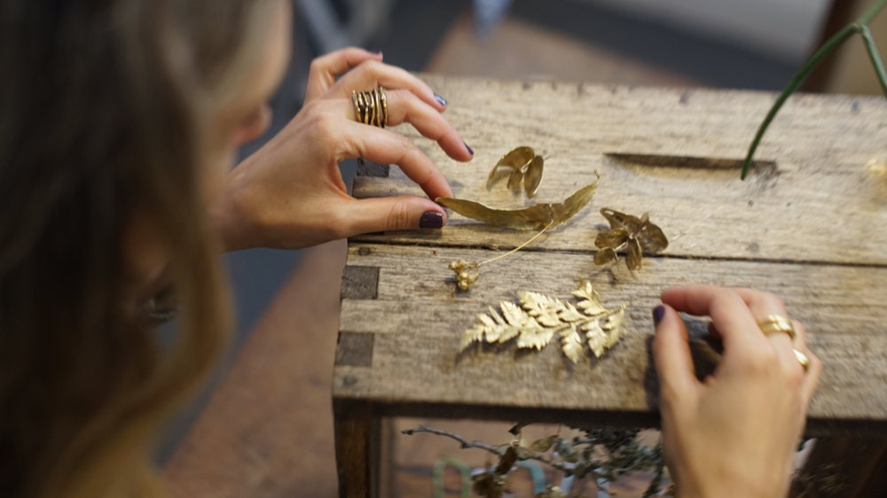 Maria assembles delicate botanical jewelry in her studio