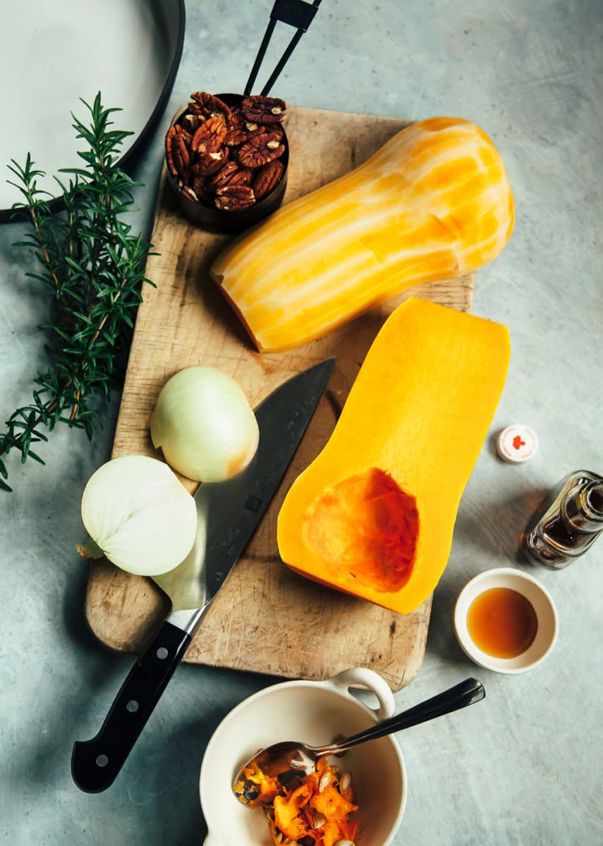 Halved butternut squash and onion laid on a cutting board, ready for slicing