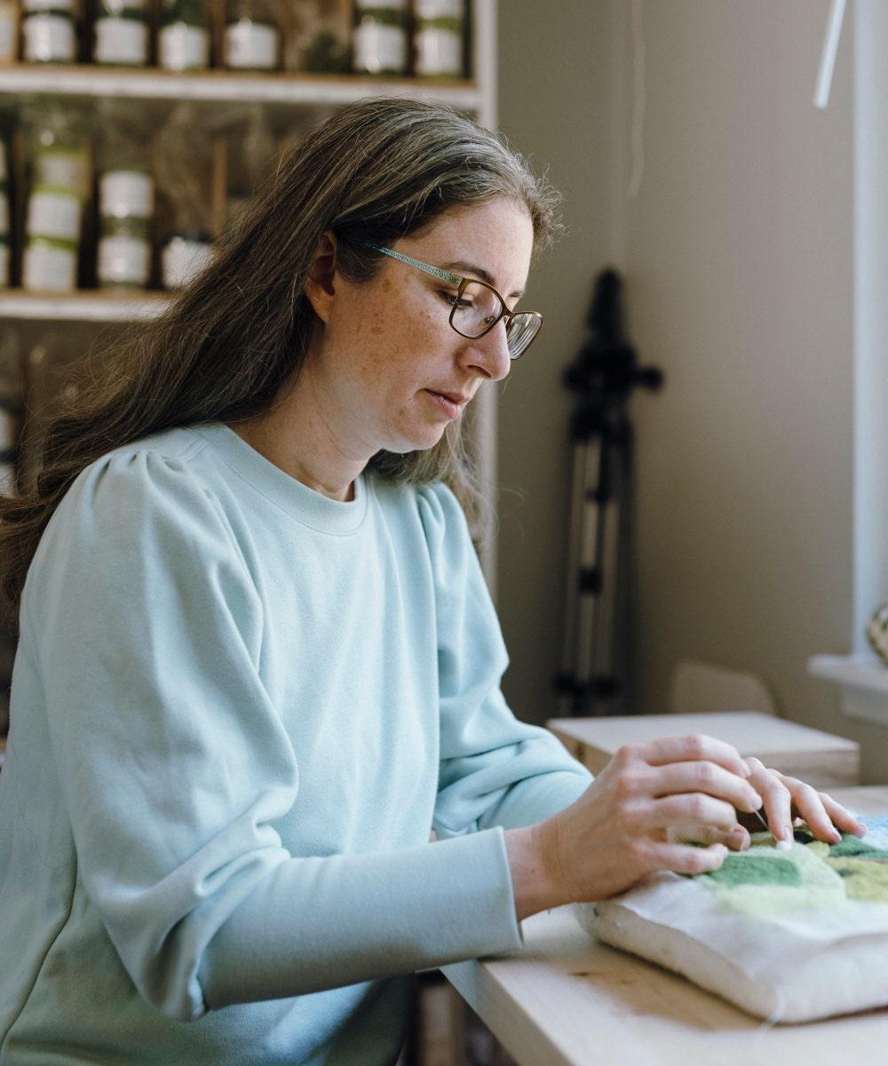 Elizabeth pokes her felting needle into a work-in-progress of her Grazing Sheep landscape