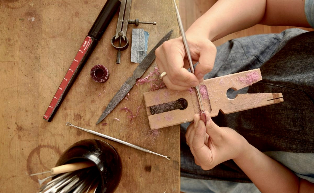 Shuang working on a piece of jewelry at her workbench