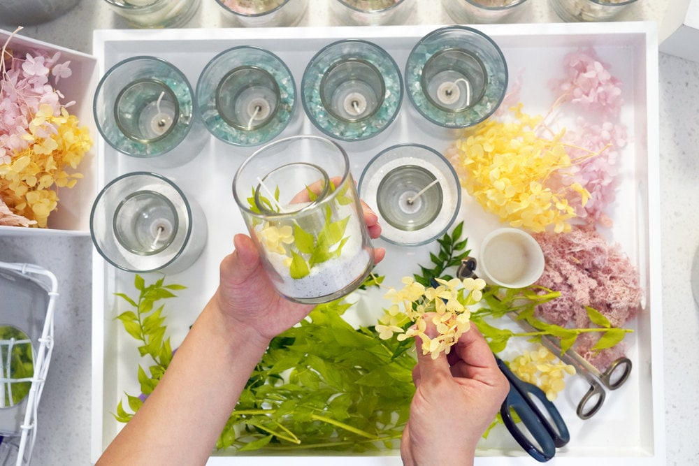 Rino adds decorative dried flowers to her glass candle base