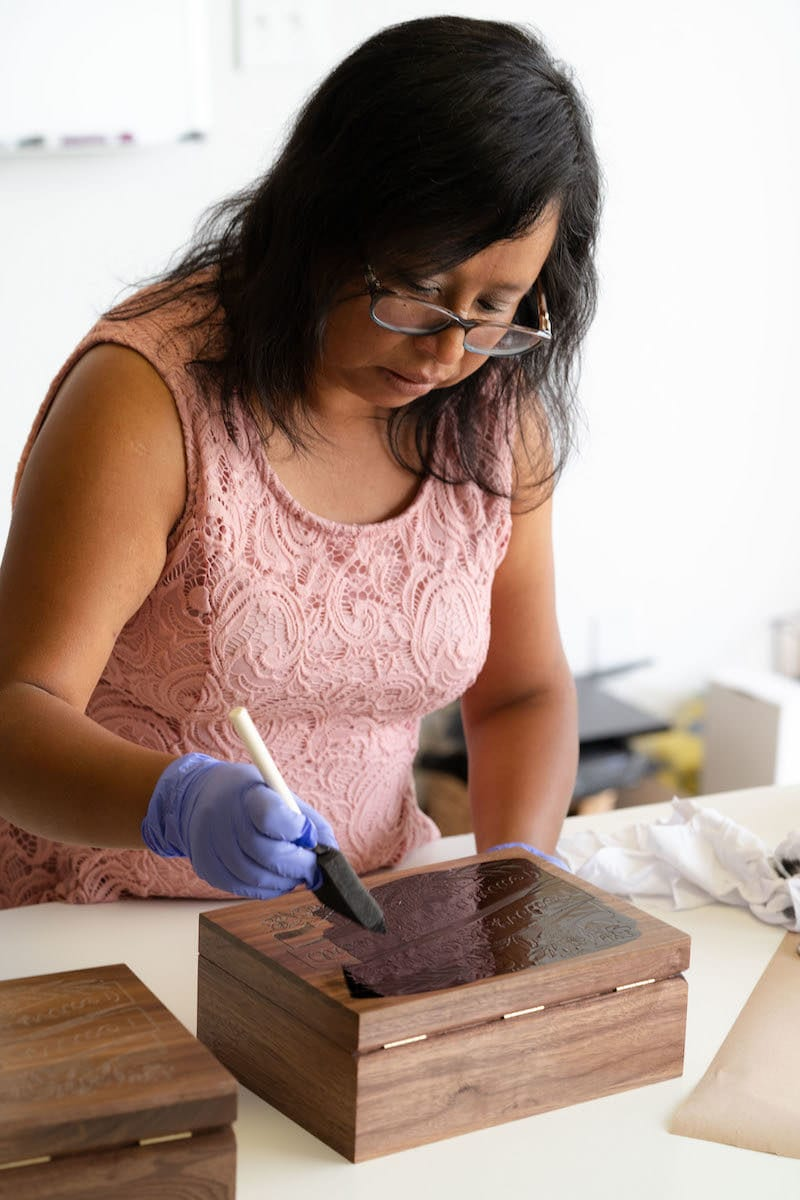 A member of the Hereafter team works on a wooden keepsake box