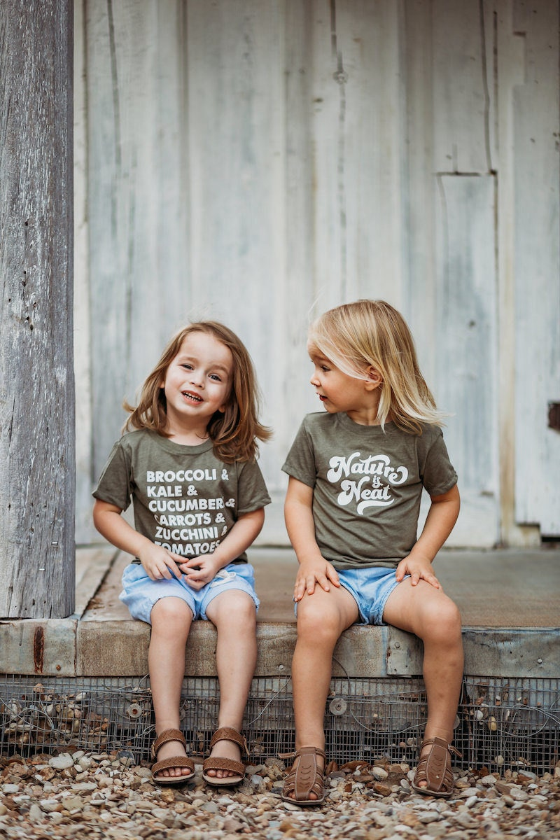 Two children sit wearing olive green T-shirts from Nature Supply Co.