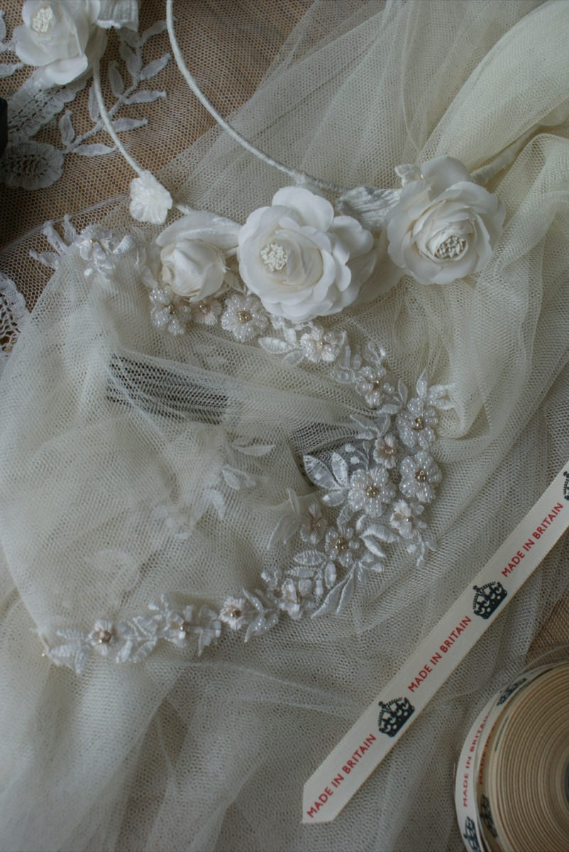 Details on a veil with a floral trim, loosely piled on Rae's workbench.