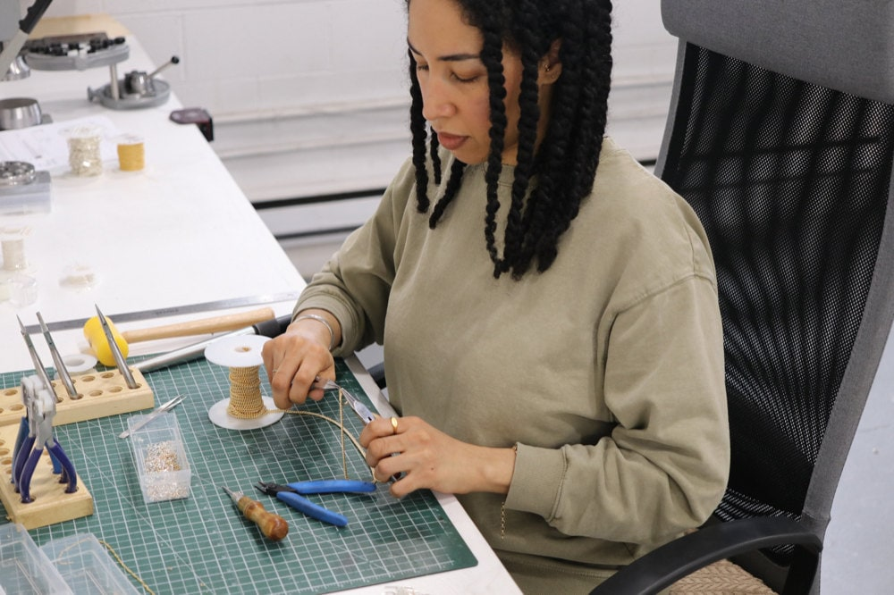 Sabrina at her work bench assembling a gold necklace.