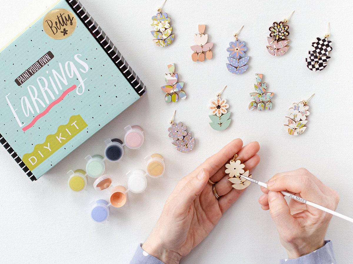 A model paints statement earrings using a DIY kit.