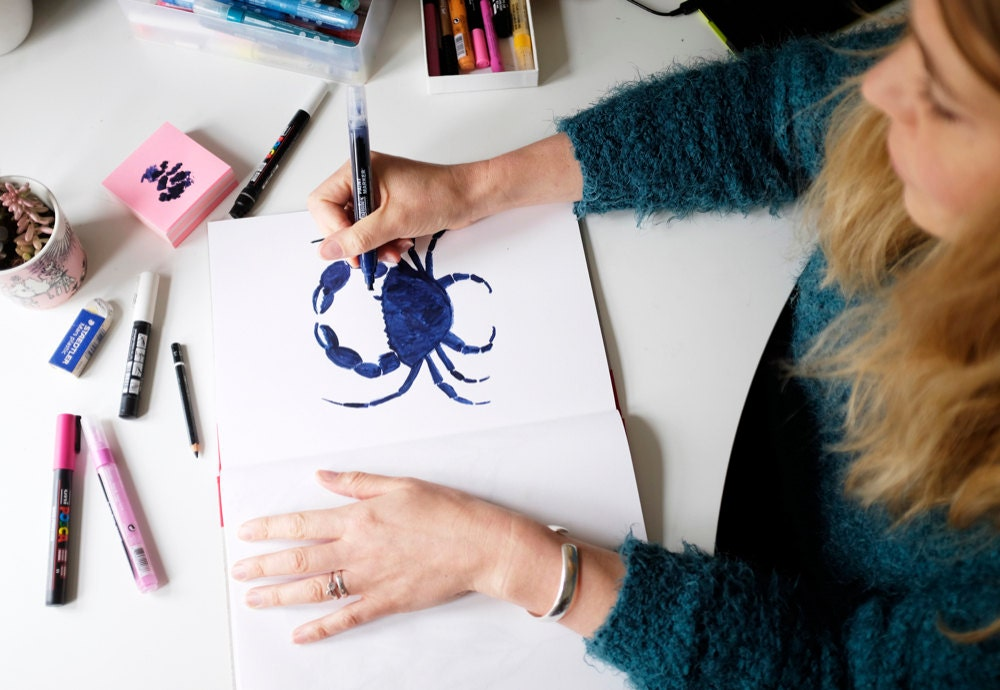 Lee draws a crab design in her notebook with a blue marker