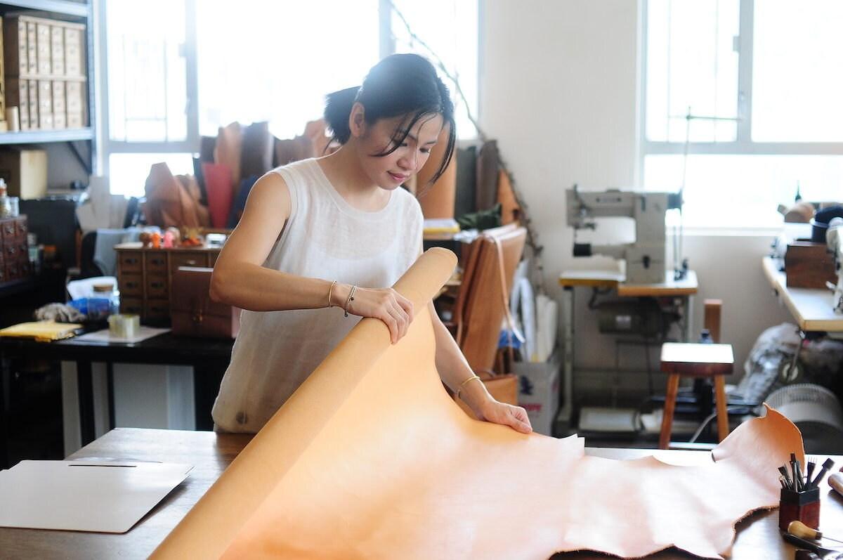 Joe unfurling a roll of leather in her studio