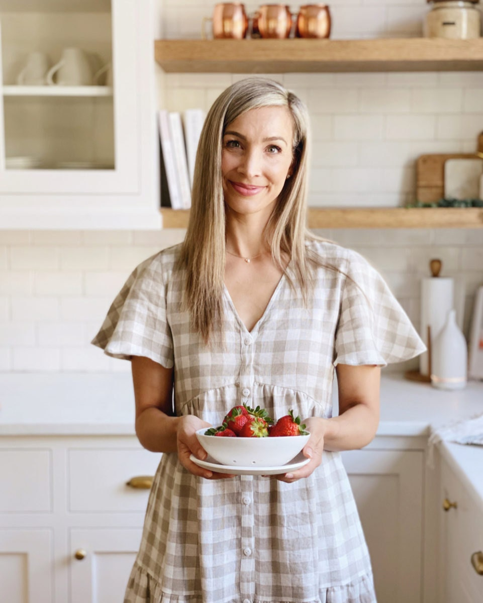 Kristine poses in the kitchen holding a berry bowl from Etsy and wearing a checkered linen dress from Etsy.