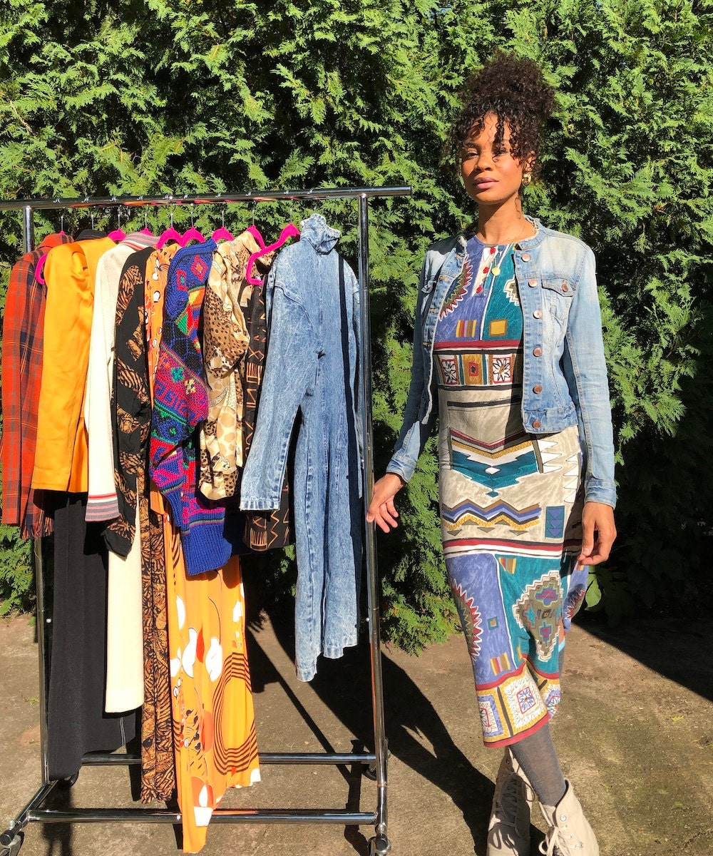 A portrait of Halima Garrett, owner of vintage clothing shop Threads of Habit, with a rack of her colorful garments.