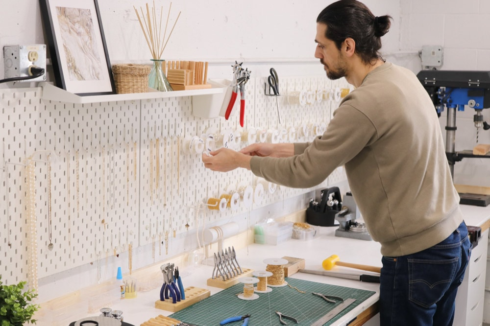 Sabrina's partner, Abe, organizing various spools of gold and silver chains above the studio workbench.