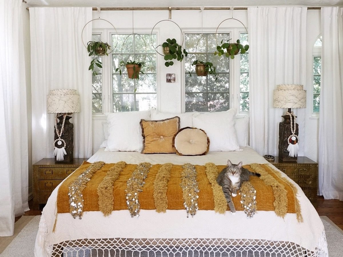 A bright bedroom interior featuring hanging planters, a bed covered with an orange blanket and framed by two nightstands, and a cat