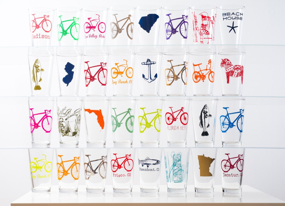 Four rows of neatly stacked pint glasses featuring an assortment of colorful printed illustrations, from fish and bicycles to horses and states.