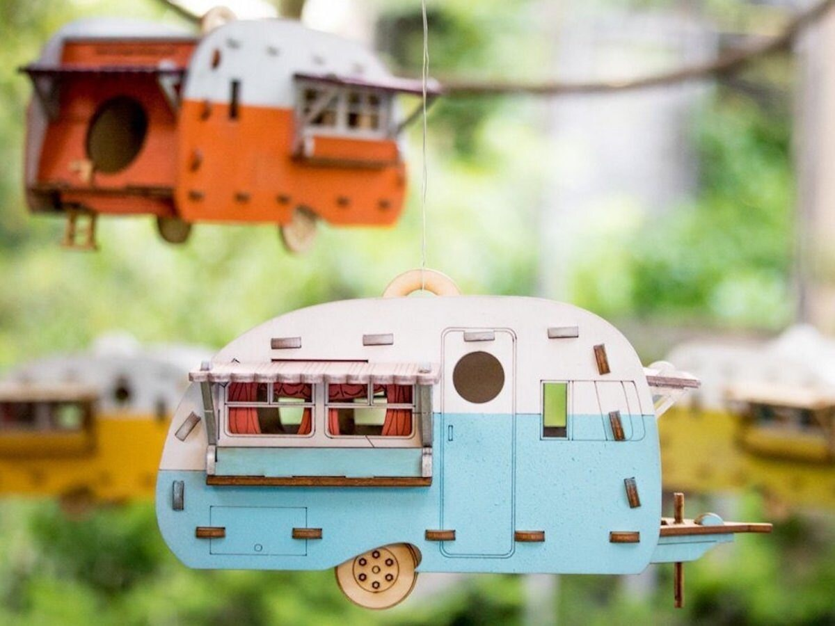 Two camper-style birdhouses hanging from a tree.