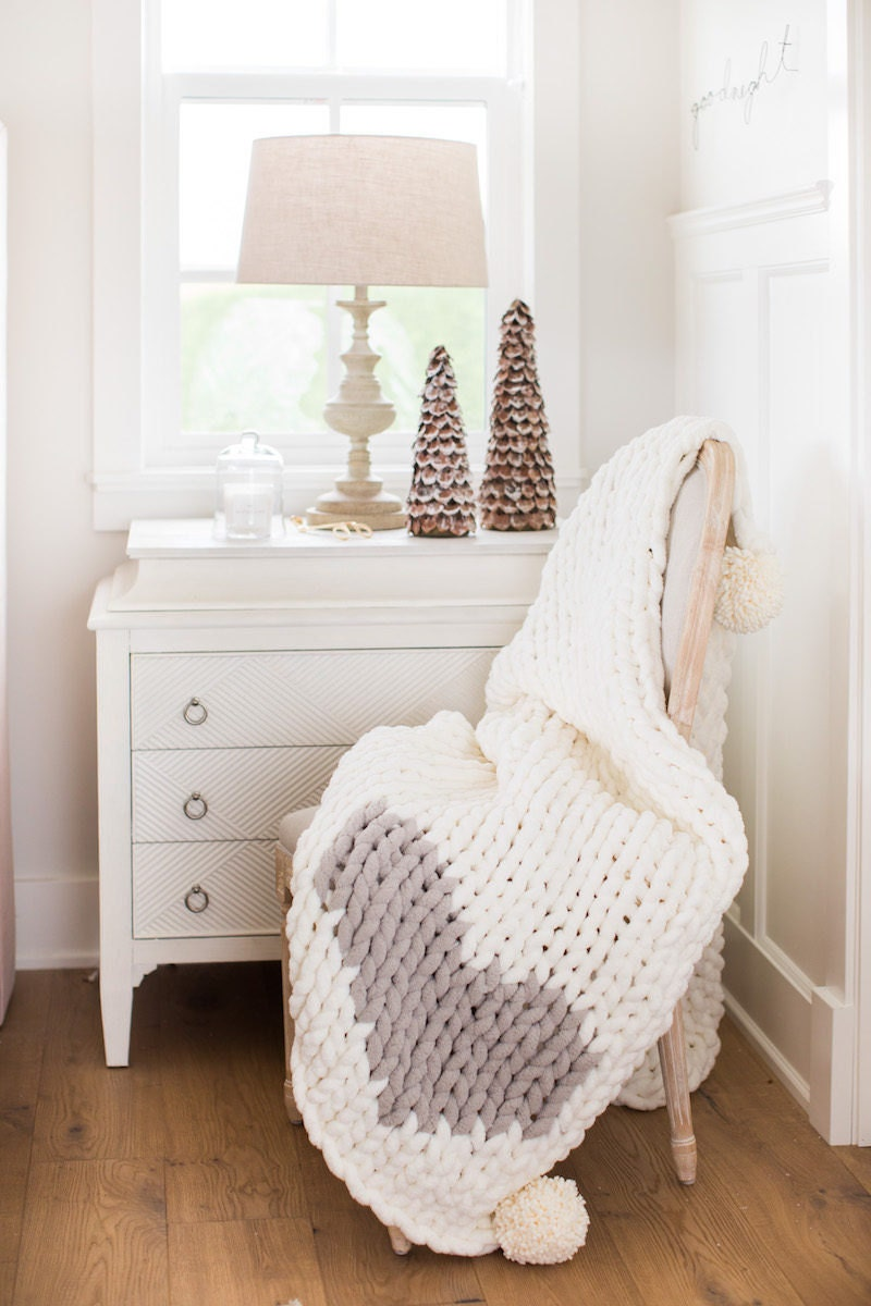 White chunky knit blanket draped over a chair in front of a bedroom window