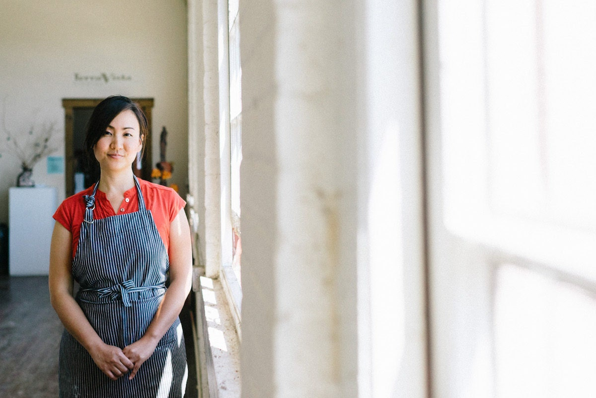 Yumiko stands next to the windows in her studio