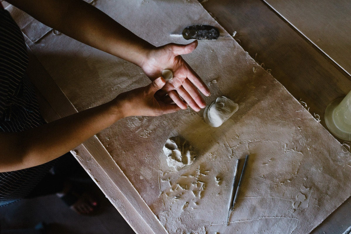 Yumiko forms a piece of clay to adorn one of her vessels