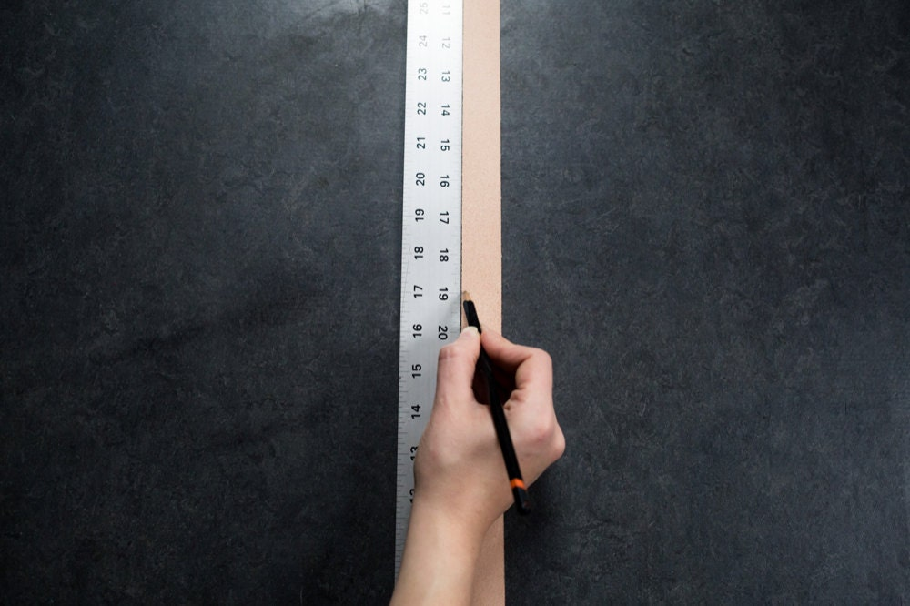 Measuring the leather straps alongside a ruler and marking off the correct length with a pencil