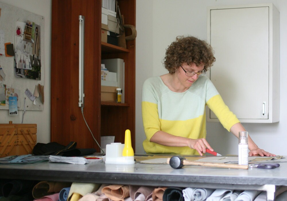 Alex cutting leather at her workbench
