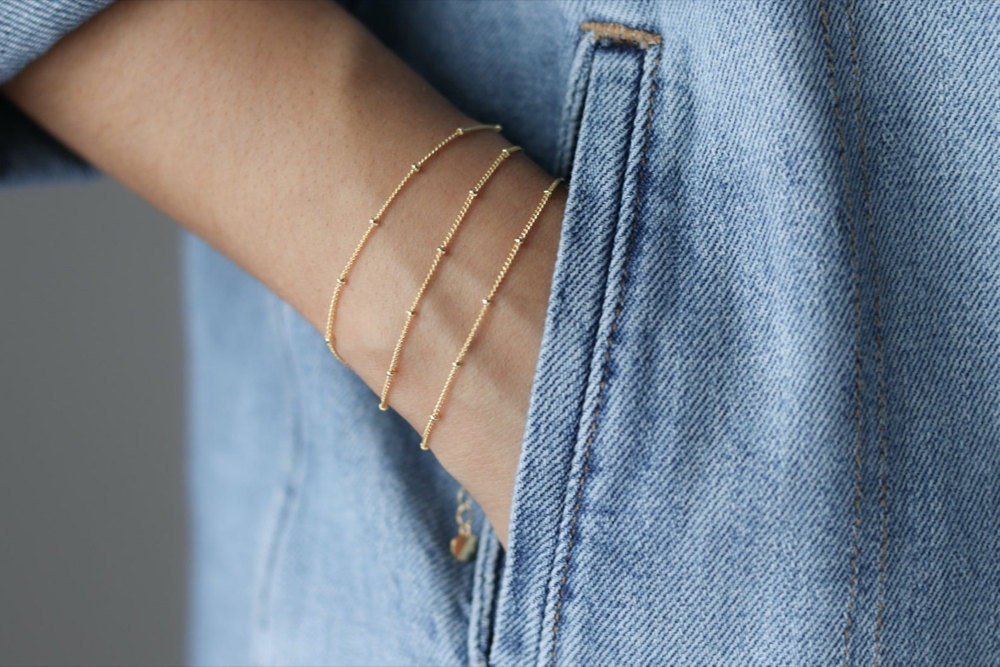 A woman wears a stack of 3 dainty beaded gold bracelets.