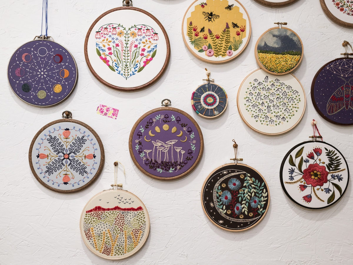 A wall adorned with completed Cozy Blue embroidery hoops