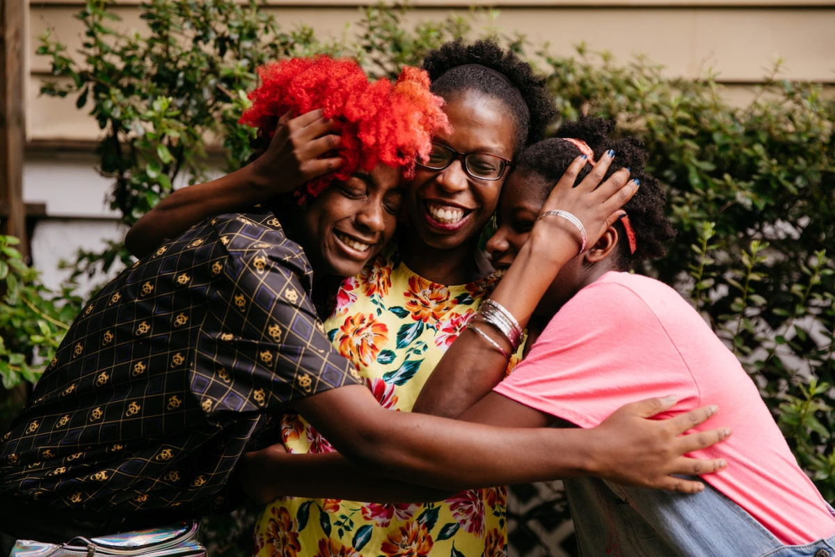 Mirlande embraces her two daughters
