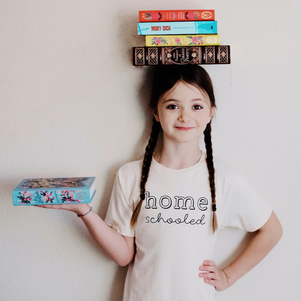 """A girl wearing a """"Homeschooled"""" T-shirt from Nature Supply Co., with a stack of books balanced on her head"""
