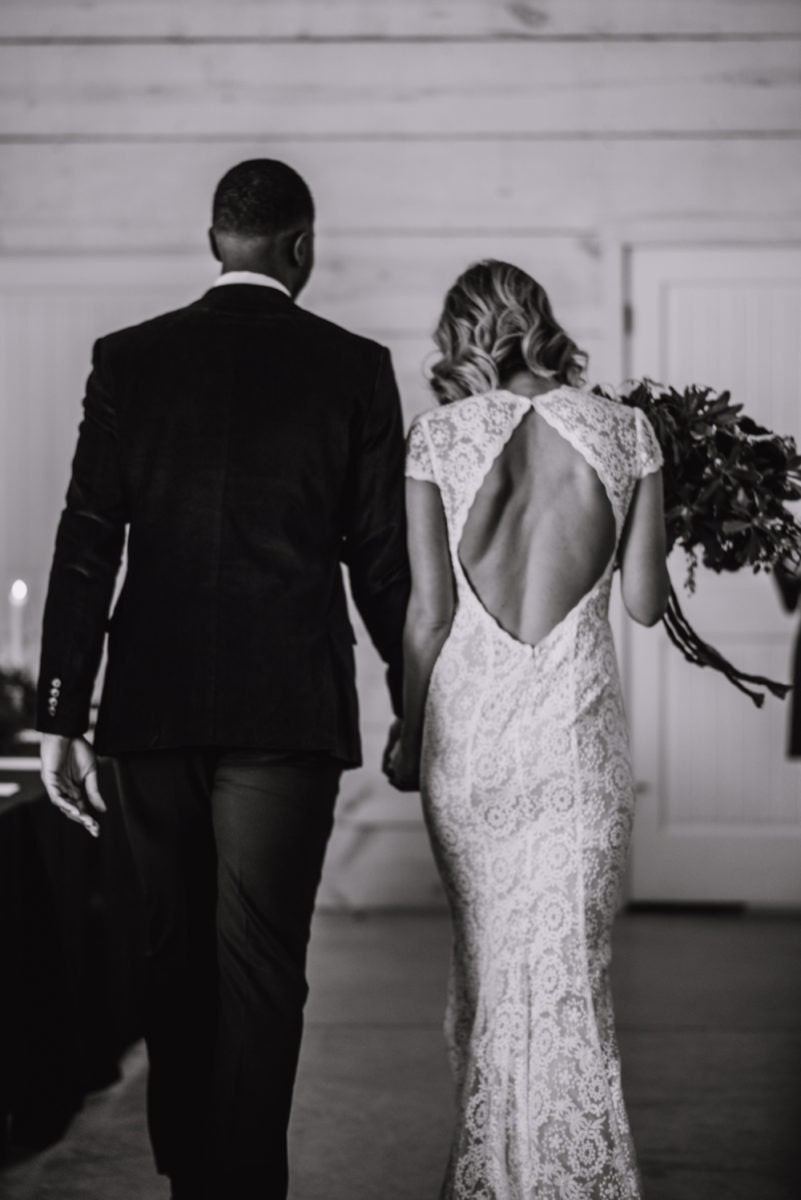 A black and white photo of Emily and Terrell from behind as they recess down the aisle