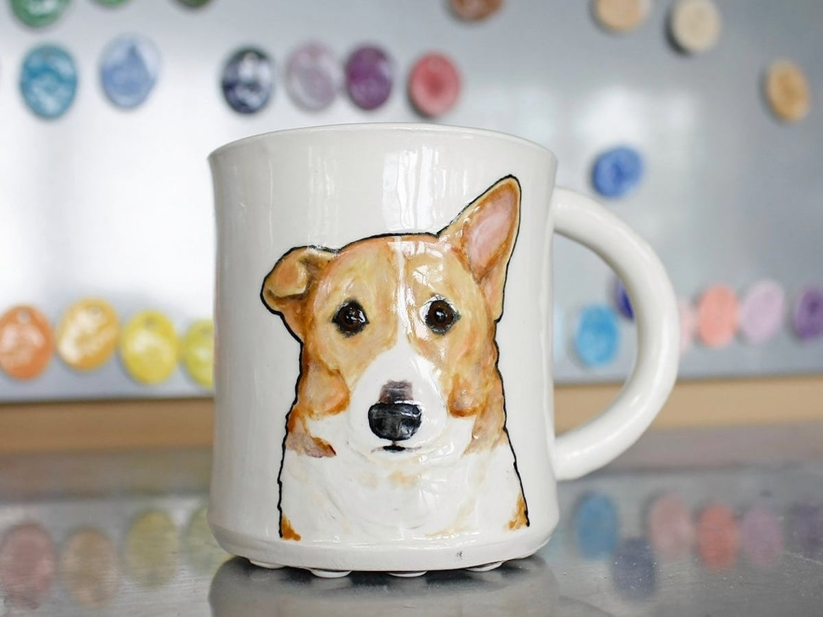 A hand-sculpted pet portrait mug from Hadley Clay featuring a Corgi in 3D relief. One of the 2020 Etsy Design Awards finalists.