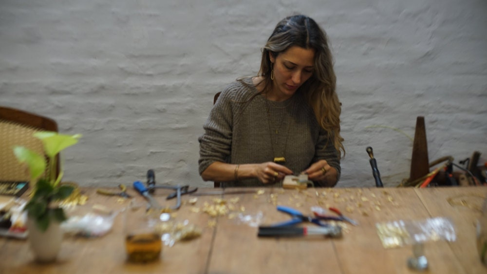 Maria creating jewelry at her workbench