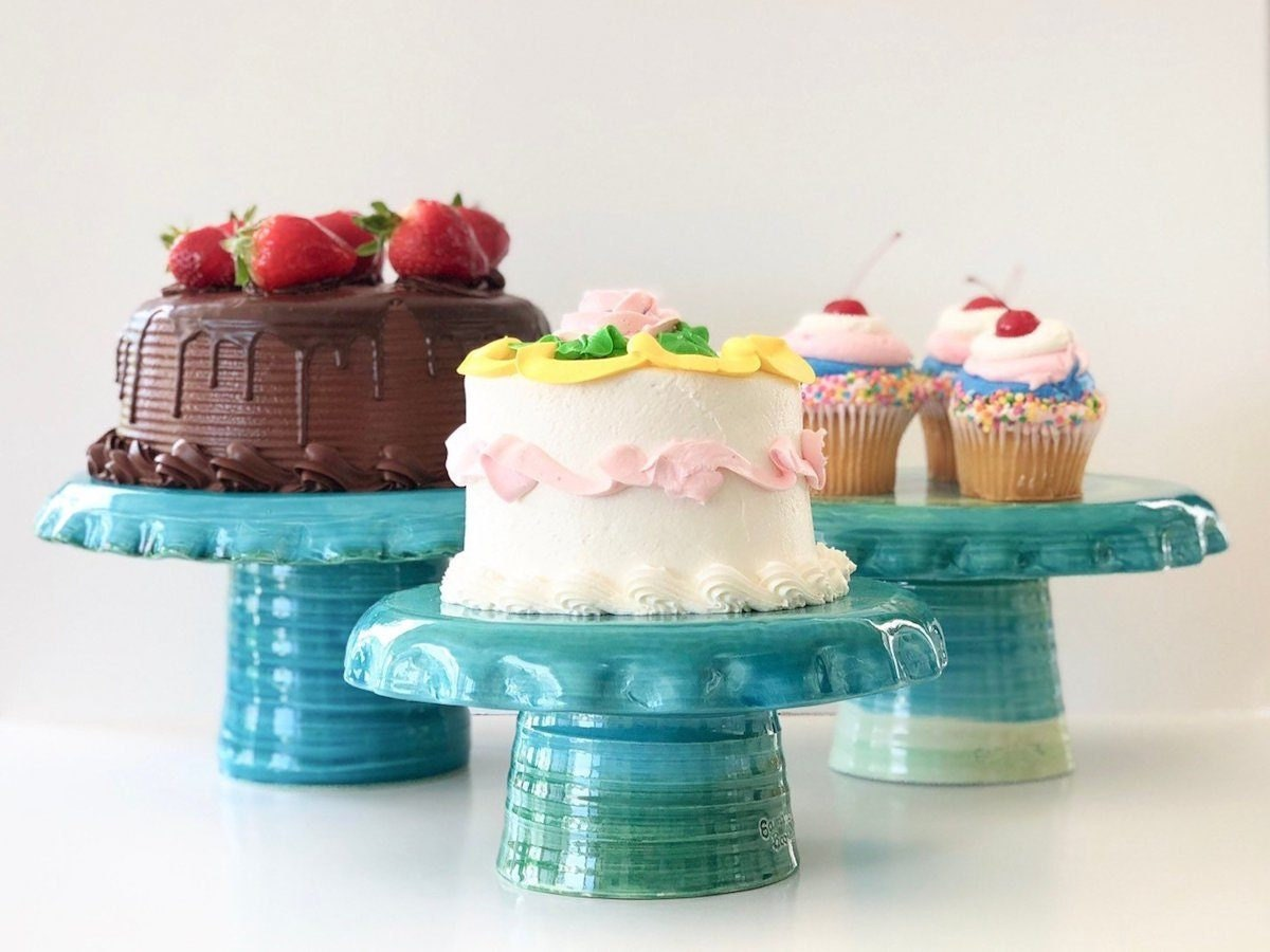 A trio of turquoise ceramic cake stands displaying fancy cakes.