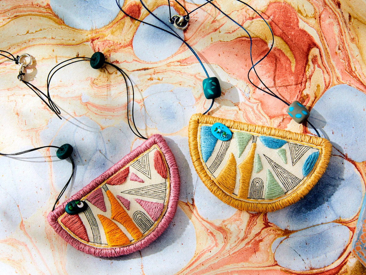 Two geometric embroidered bib necklaces from Perrrce styled on a colorful marbled paper backdrop