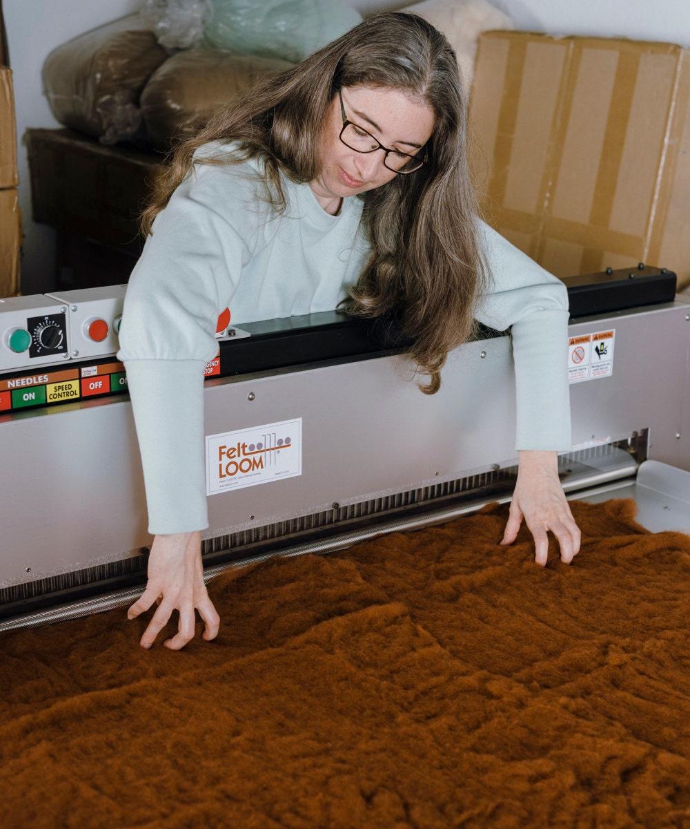 Elizabeth lays out wool on a felt loom.