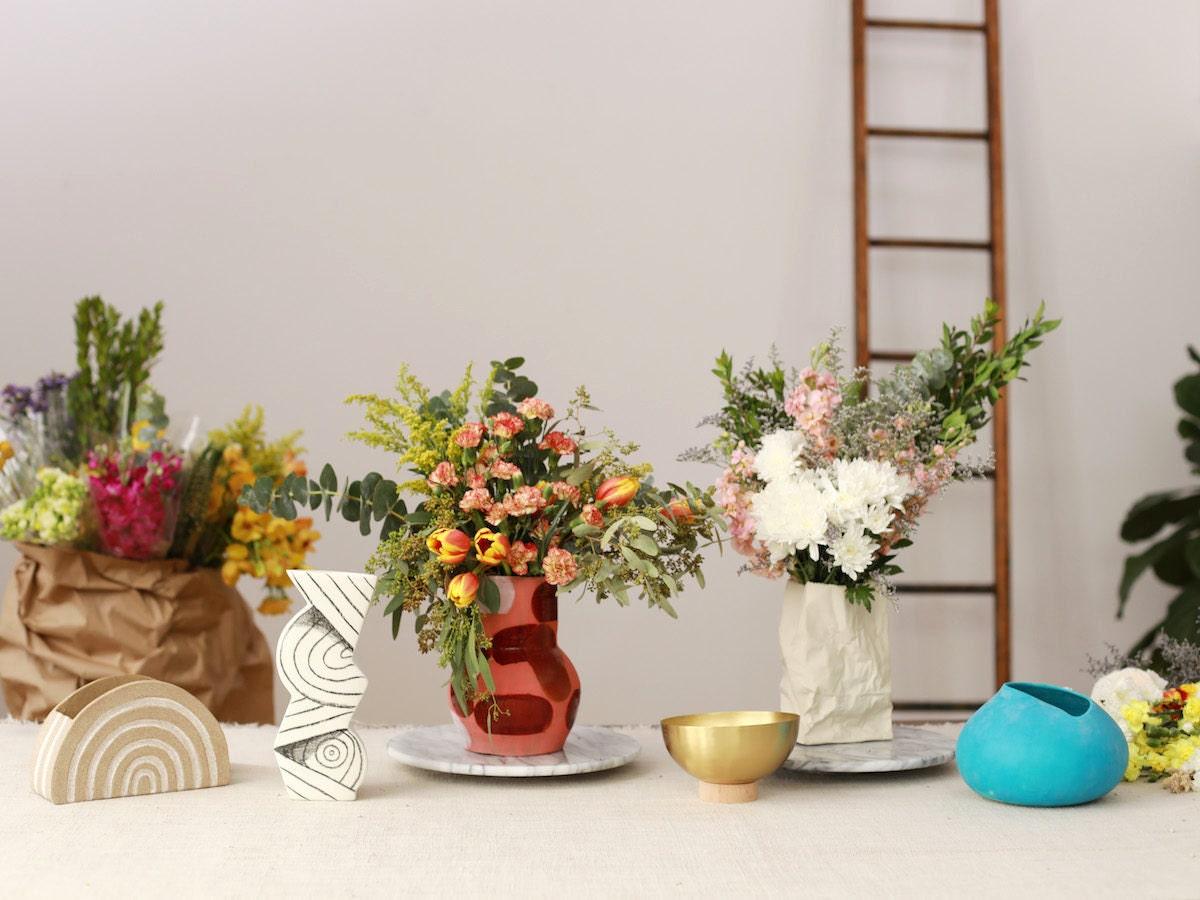 Floral arrangements in Etsy vases on display