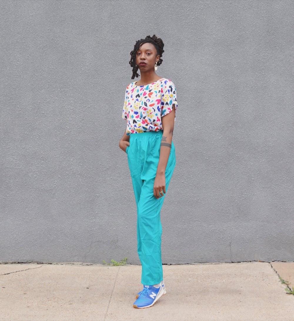 Rachelle models a colorful top nd bright blue pants.