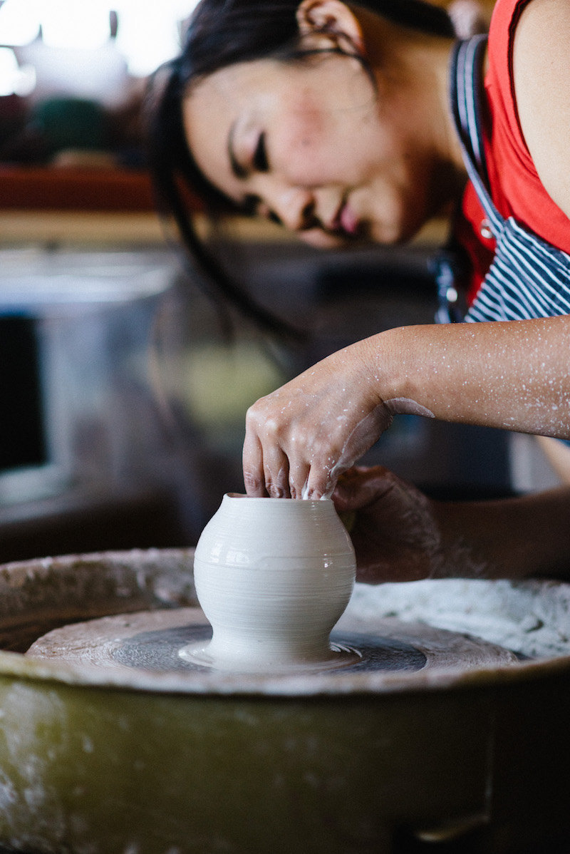 Yumiko throws a piece on her pottery wheel