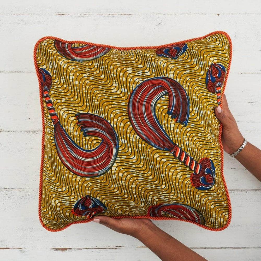 A gold and orange throw pillow cover from Bespoke Binny