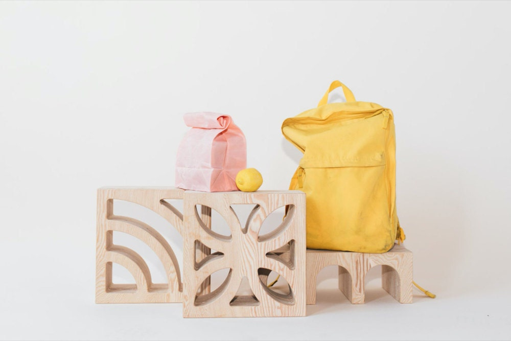 A styled photo of decorative tinder blocks, wine racks, and lunch bags.