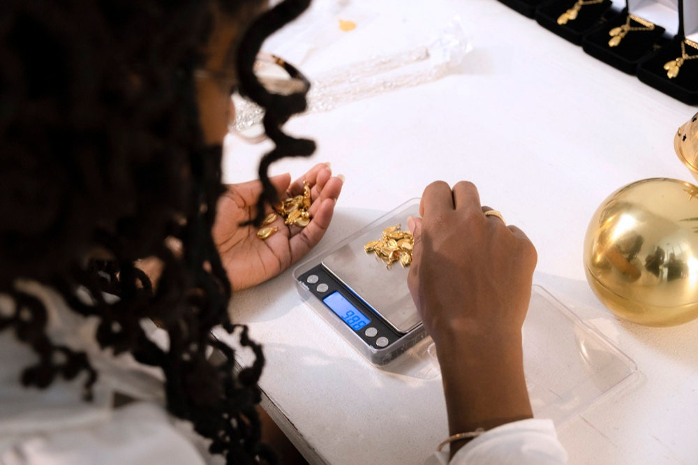 Ashley weighs cowrie shell charms on a scale